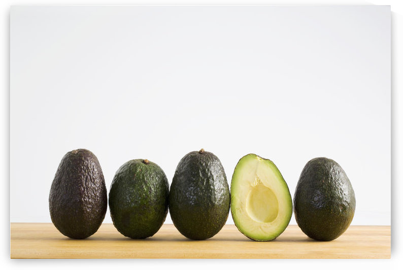A Row Of Avocados Standing Upright On A Wooden Board With One Cut In Half Without The Pit; Calgary, Alberta, Canada by PacificStock