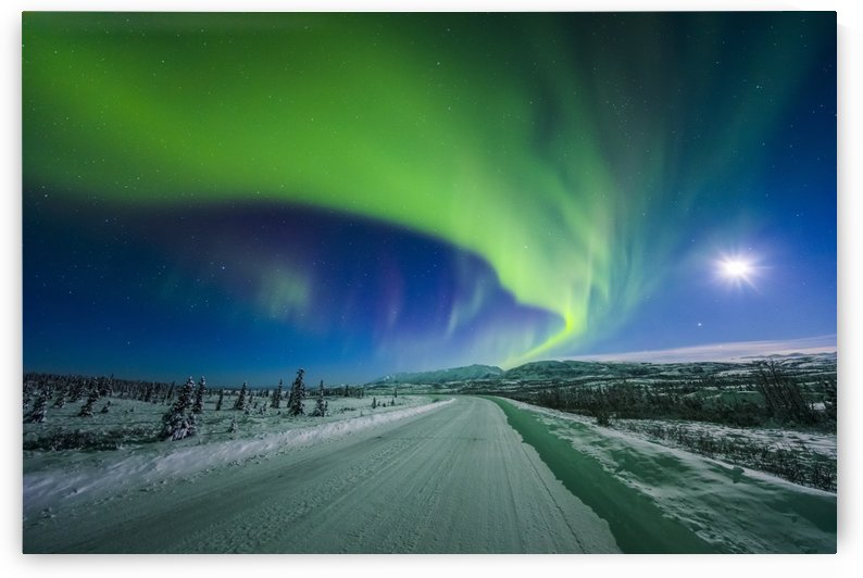 The moon and aurora shine in the night sky over a snow covered Richardson Highway south of Delta Junction; Alaska, United States of America by PacificStock