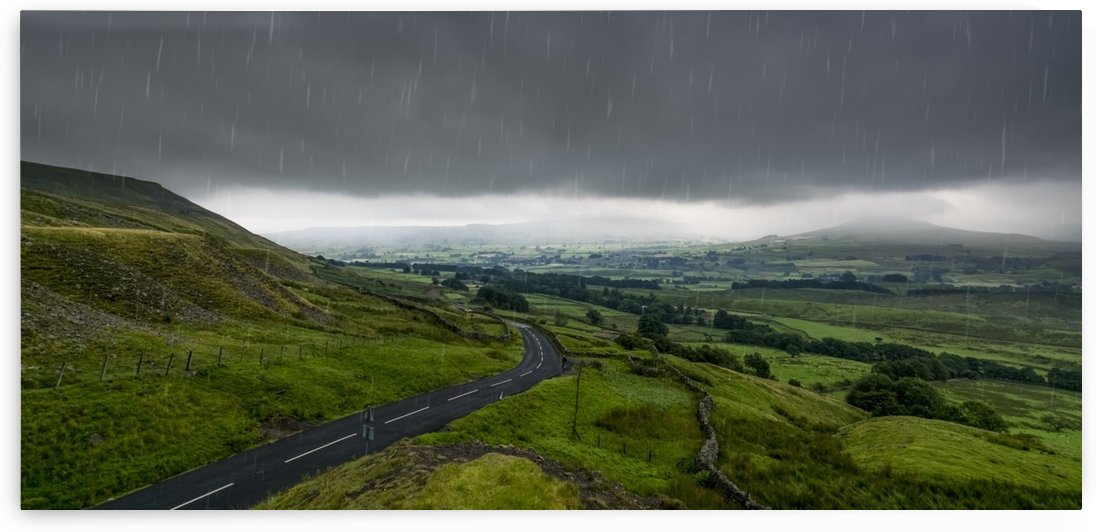 Rain falling from a stormy sky over a lush, green landscape; North Yorkshire, England by PacificStock