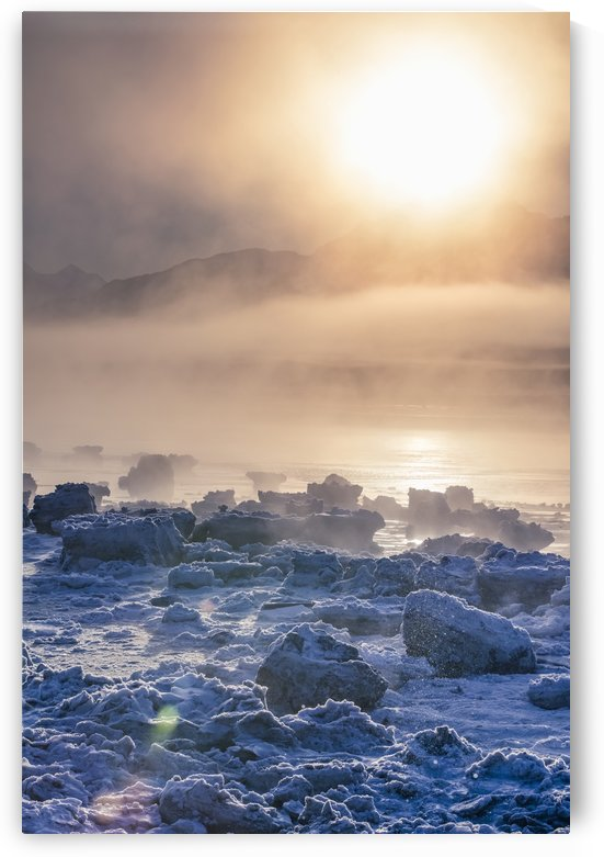Low altitude fog is cast in warm sunset light along Turnagain Arm and the Seward Highway in winter, sea ice covering the ocean in the foreground, the Chugach Moutains revealed in the background, South-central Alaska; Alaska, United States of America by PacificStock