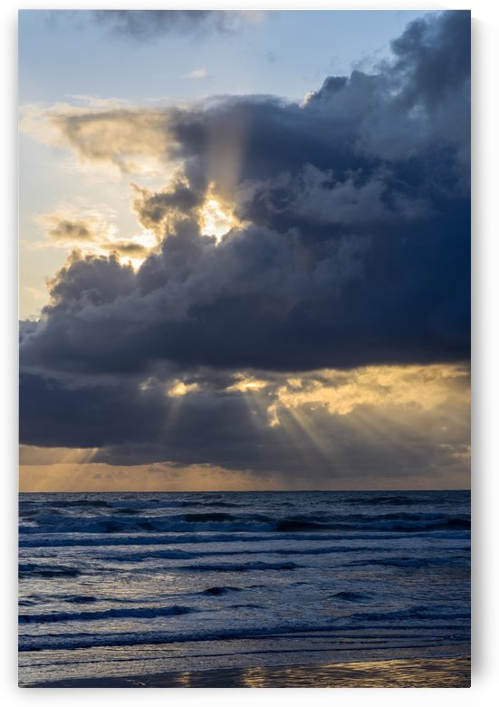 Sunbeams flow through holes in the clouds along the Oregon Coast; Cannon Beach, Oregon, United States of America by PacificStock