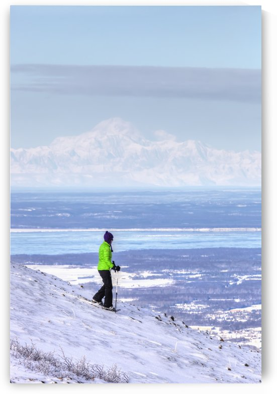 Woman snowshoeing on Blueberry Hill at the Glen Alps area of Chugach State Park with Mt. McKinley (Denali) in the background, Anchorage, Southcentral Alaska, Winter, HDR by PacificStock