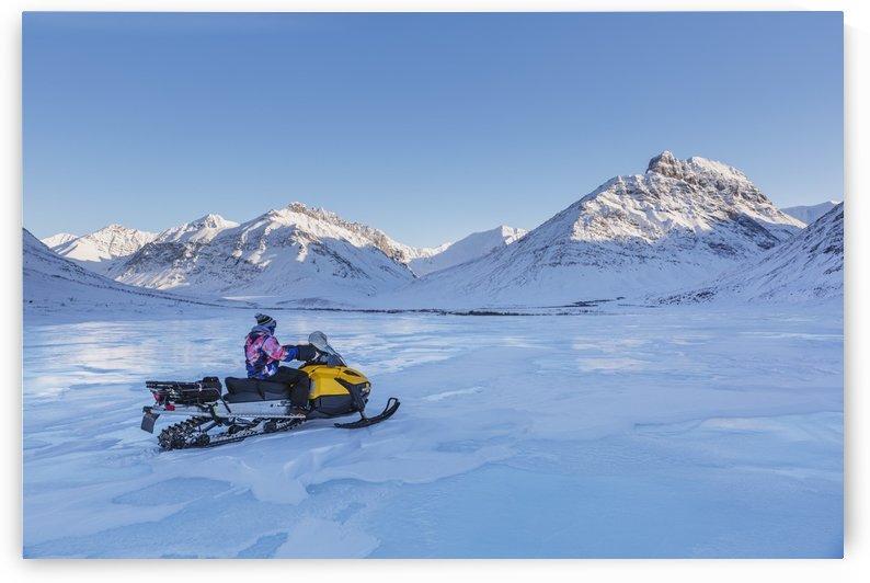 Native youth riding Snowmachine on overflow ice, Inukpasugruk (Giant) Creek, Anaktuvuk Pass, Gates of the Arctic National Park, Brooks Range, Northern Alaska, USA. by PacificStock