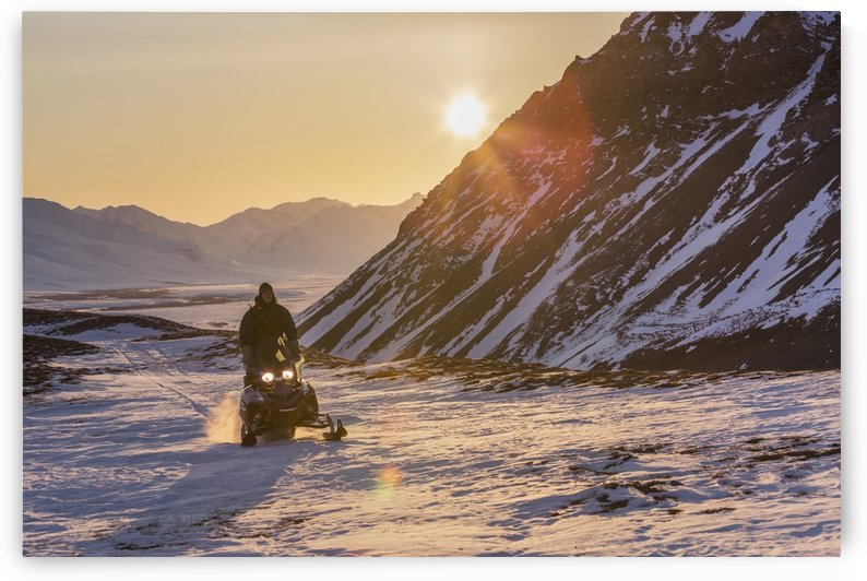 Man riding a snowmachine up the Anaktuvuk River Valley at sunset, Gates of the Arctic National Park, Brooks Range, Arctic Alaska by PacificStock