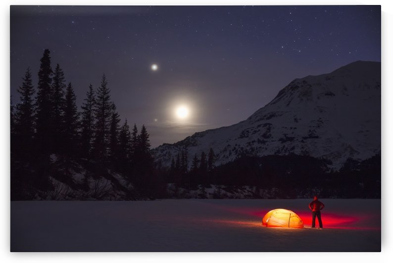 Nighttime view of a man standing next to a lit tent on a snow covered Trail Lake with the moon, stars, and planets overhead, Moose Pass, Kenai Peninsula, Southcentral Alaska by PacificStock