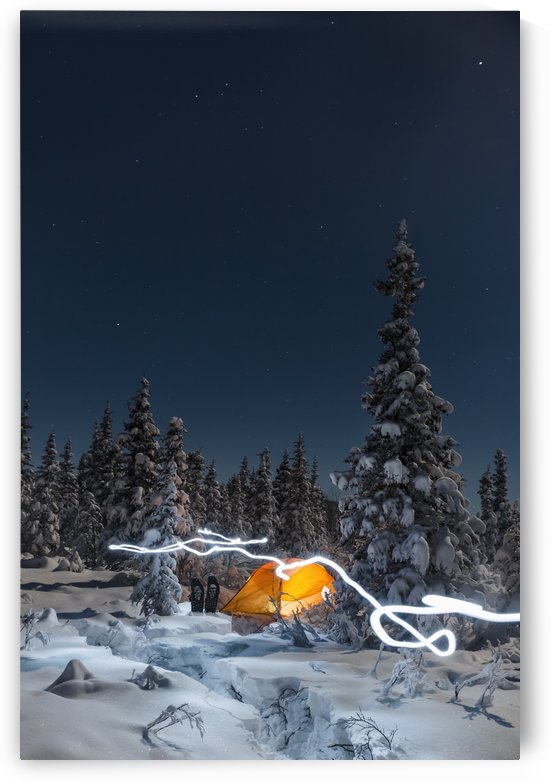 A trail of light leads past an orange tent in the middle of an snowy evergreen forest, snowshoes outside the tent, moonlight casting shadows on a clear winter night,  Interior Alaska; Gakona, Alaska, United States of America by PacificStock