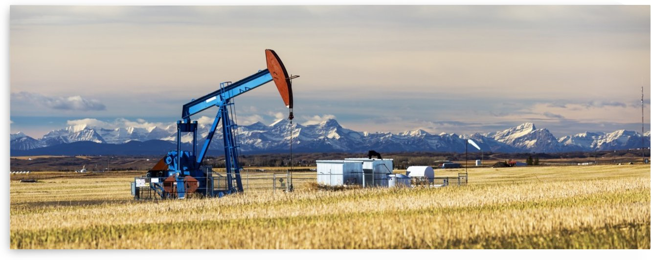 Panorama of a colourful pump jack in cut canola stubble field with snow capped mountains, blue sky and clouds in the background; Alberta, Canada by PacificStock