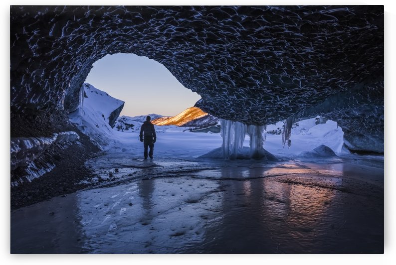 A man walks out the entrance of an ice tunnel at the terminus of Canwell Glacier in the Alaska Range in mid-winter; Alaska, United States of America by PacificStock