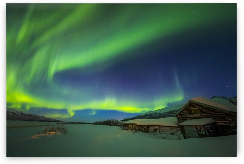 The aurora fills the sky above the historic Black Rapids Roadhouse along the Richardson Highway on a bitterly cold night; Alaska, United States of America by PacificStock