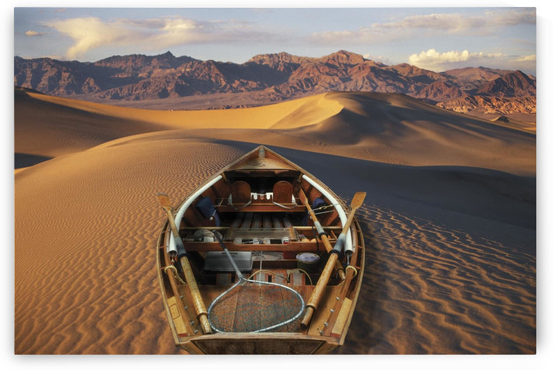 Drift Boat Resting On Sand Dunes In Death Valley National Park Representing Global Warming. Digital Composite by PacificStock