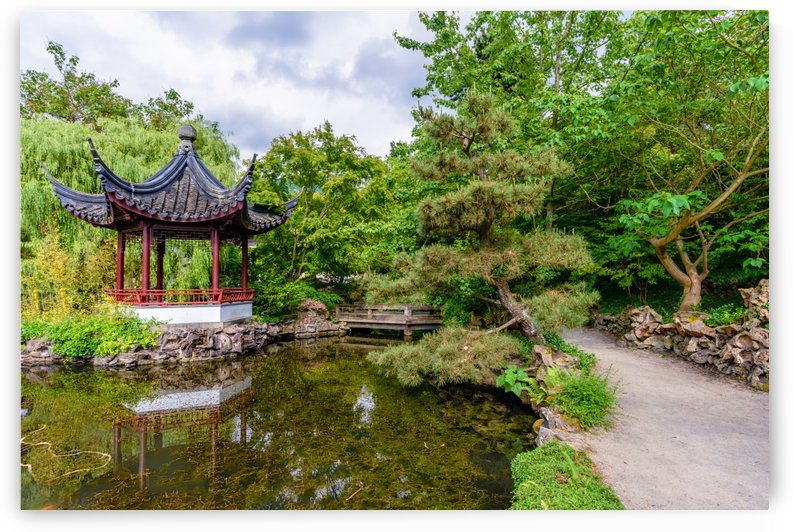 path near a pond with a wooden bridge and a pavilion reflected in it in a Chinese garden by Viktor Birkus