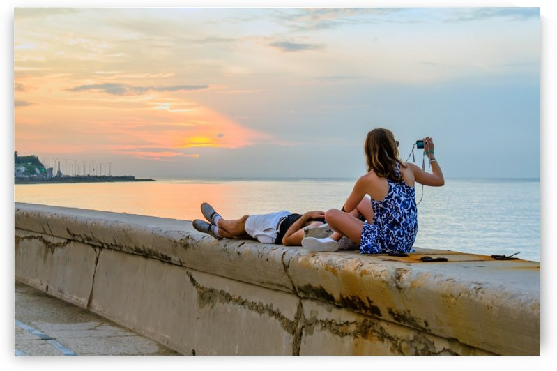 Young couple watching and photographing the sunset on the ocean by Viktor Birkus