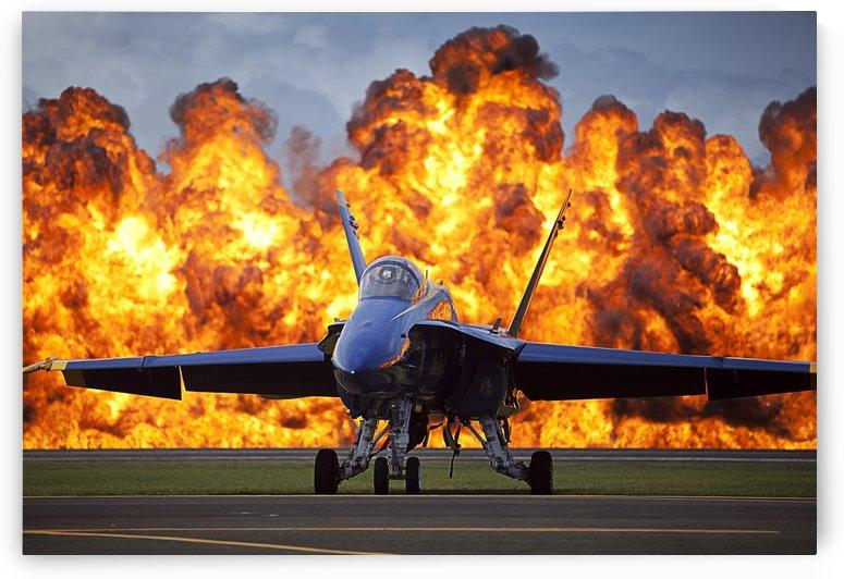 A wall of fire erupts behind a U.S. Navy F-A-18 Hornet aircraft. by StocktrekImages