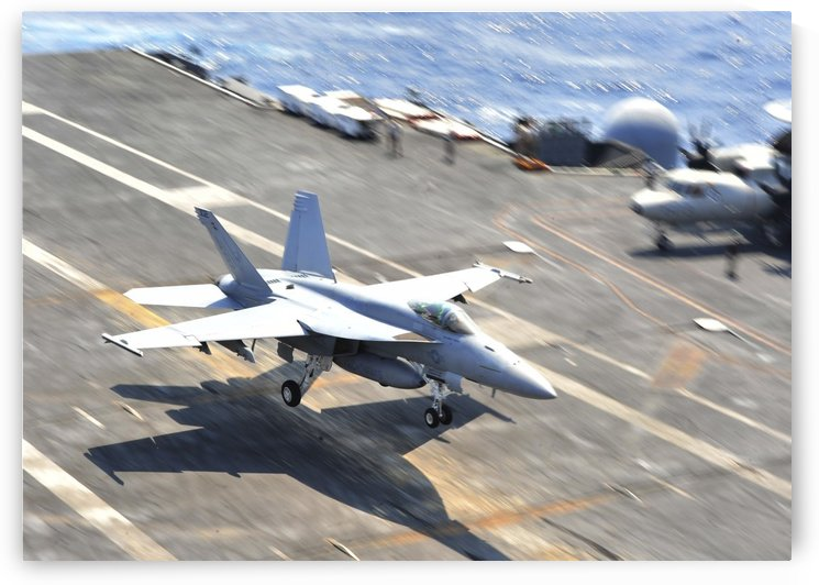 An F-A-18E Super Hornet lands aboard the aircraft carrier USS Enterprise. by StocktrekImages