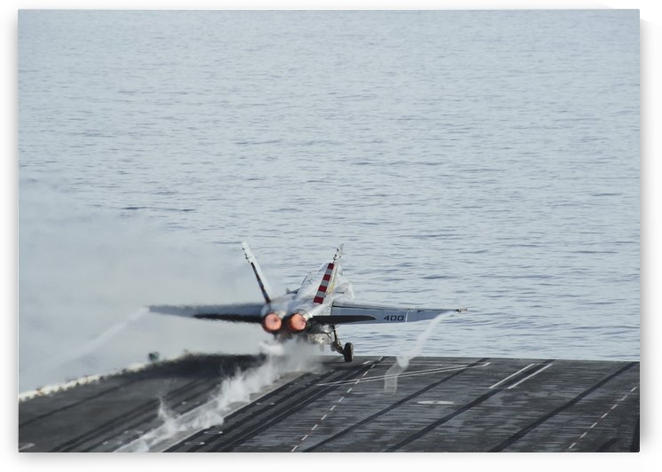 An F-A-18C Hornet takes off from the flight deck of USS Theodore Roosevelt. by StocktrekImages