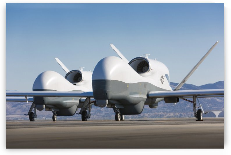 Two MQ-4C Triton unmanned aerial vehicles on the tarmac. by StocktrekImages