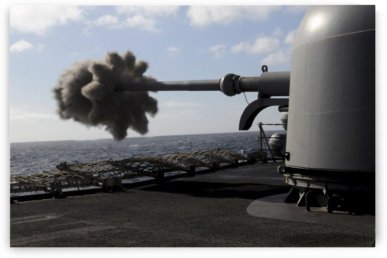 A 76mm cannon is fired aboard the guided missile frigate USS Simpson. by StocktrekImages