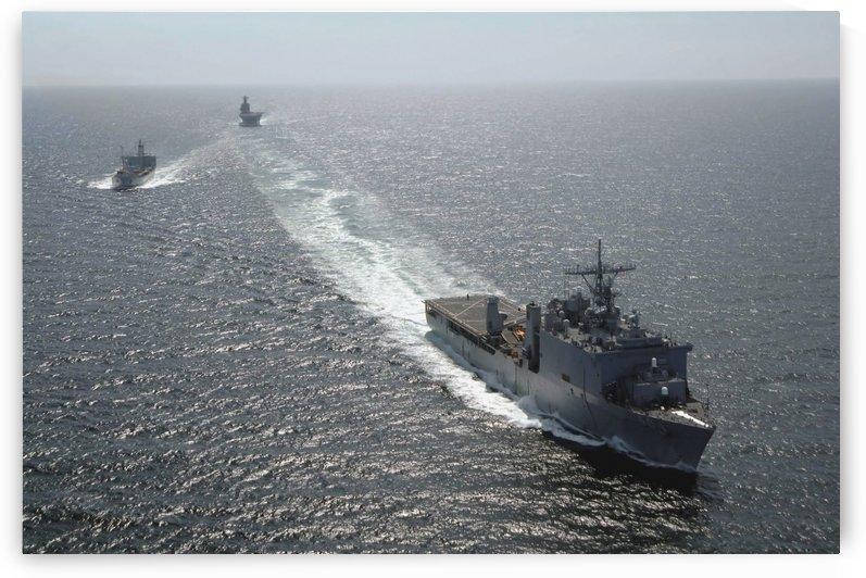 The amphibious dock landing ship USS Carter Hall breaks away following a replenishment at sea. by StocktrekImages