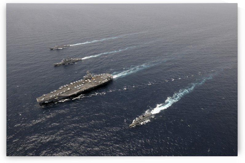 A formation of ships traveling at sea. by StocktrekImages