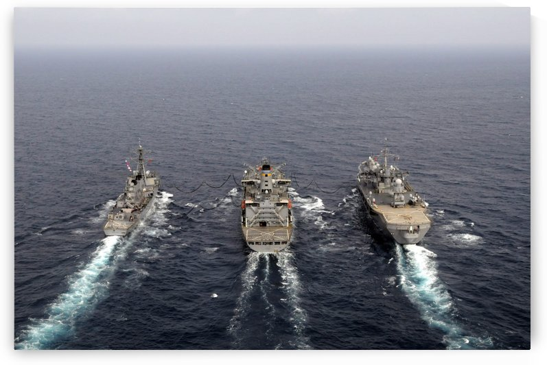 Military ships conduct an underway replenishment in the Pacific Ocean. by StocktrekImages