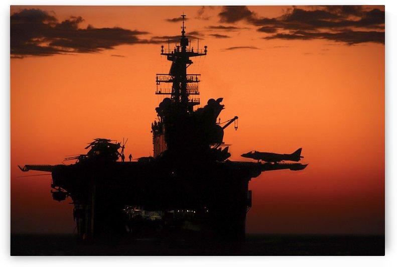 The setting sun silhouettes the amphibious assault ship USS Makin Island. by StocktrekImages