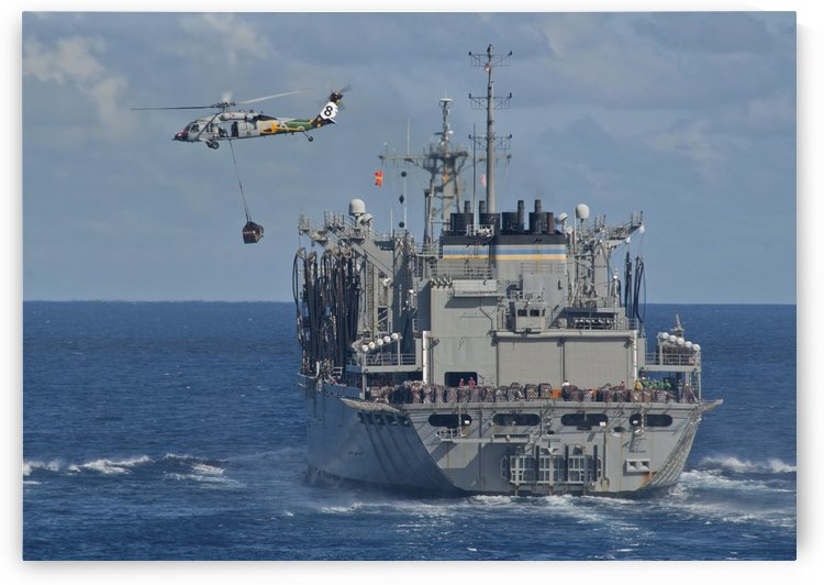 An MH-60S Sea Hawk conducts a vertical replenishment with USNS Bridge. by StocktrekImages
