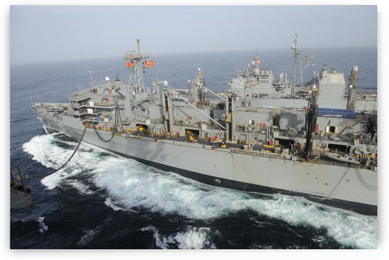USNS Rainier transits alongside USS Nimitz during a replenishment at sea. by StocktrekImages