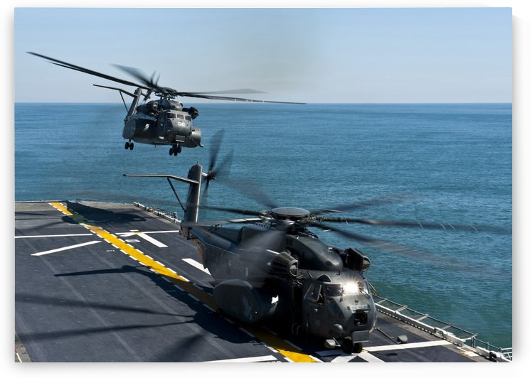 MH-53E Sea Dragon helicopters take off from the flight deck of USS Wasp. by StocktrekImages