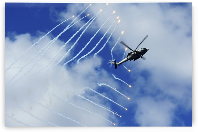 An HH-60H Sea Hawk helicopter releases countermeasure flares. by StocktrekImages