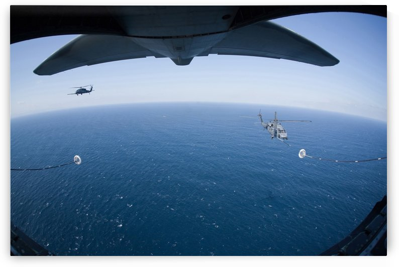 An MC-130P Combat Shadow prepares to refuel two HH-60G Pave Hawk helicopters. by StocktrekImages