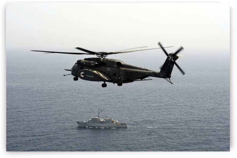 A CH-53 Sea Stallion flies above the mine countermeasures ship USS Ardent. by StocktrekImages