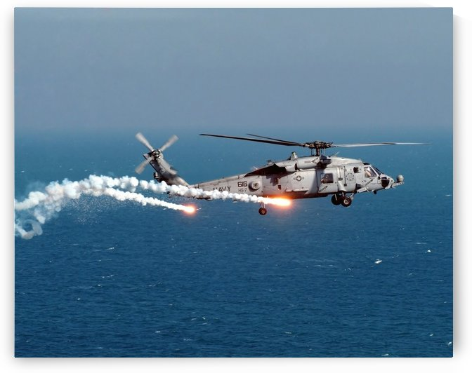 A U.S. Navy HH-60H Seahawk Helicopter dispenses flares and chaff. by StocktrekImages