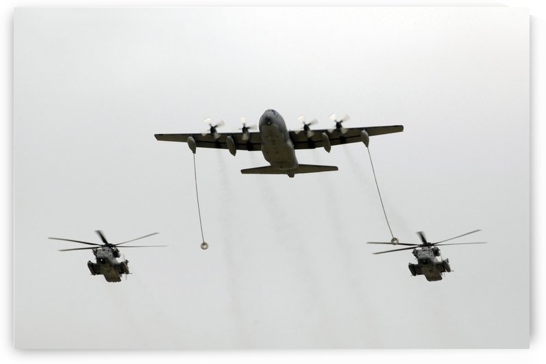 A MC-130W conducts an in-flight refueling for two MH-53J Pave Low III helicopters. by StocktrekImages