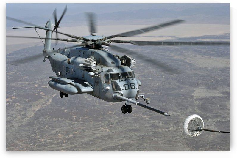 A CH-53E Super Stallion approaches a C-130P aircraft to refuel. by StocktrekImages
