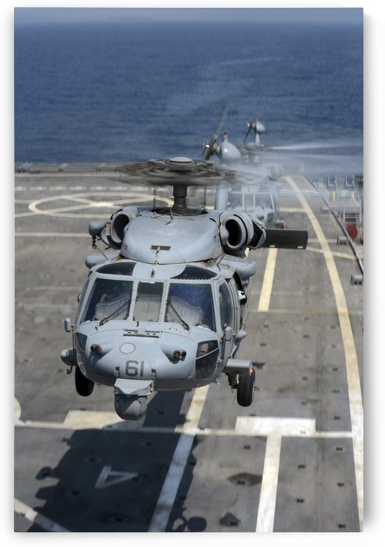 Two MH-60S Sea Hawk helicopters take off from USS Ponce. by StocktrekImages
