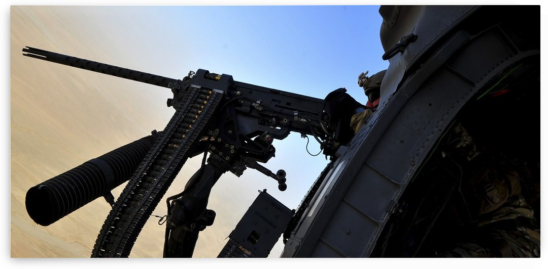Soldier mans the .50 caliber machine gun on a HH-60G Pave Hawk. by StocktrekImages