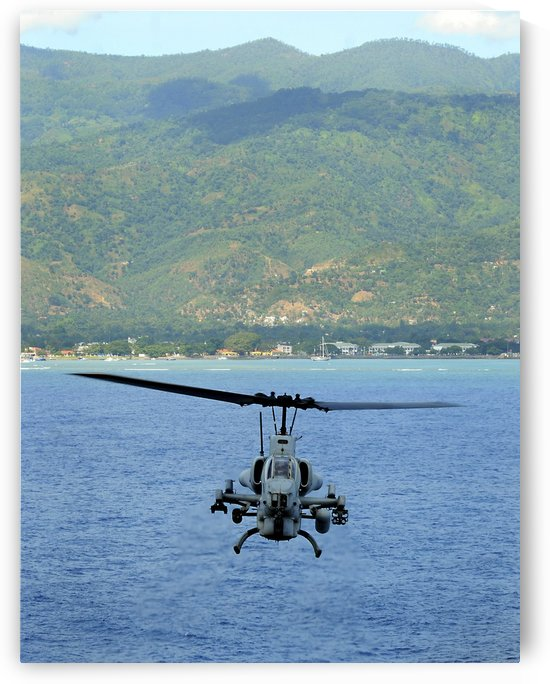 An AH-1W Super Cobra flies off the coast of Dili East Timor. by StocktrekImages