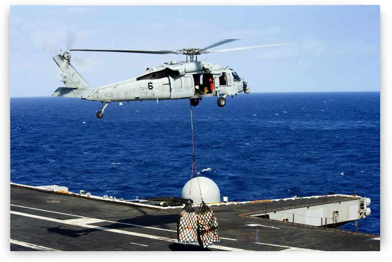 An MH-60R Seahawk helicopter places cargo onto the flight deck of USS Nimitz. by StocktrekImages
