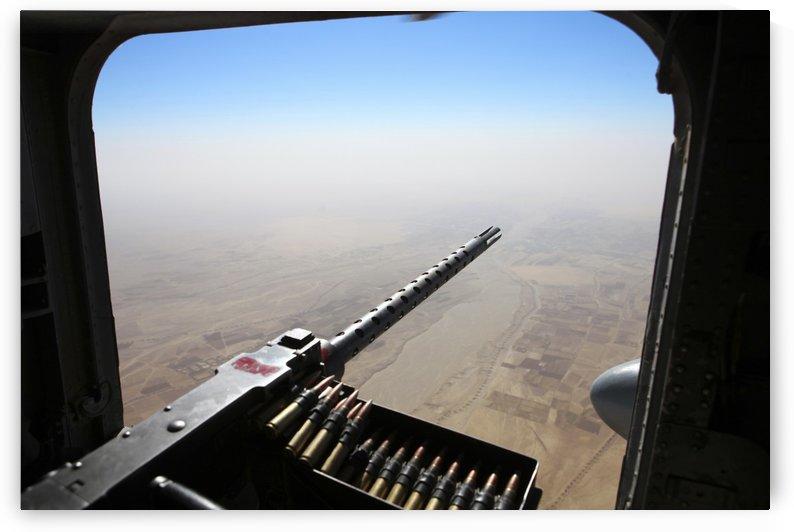 A .50 caliber machine gun aims outboard of a CH-53E Super Stallion. by StocktrekImages