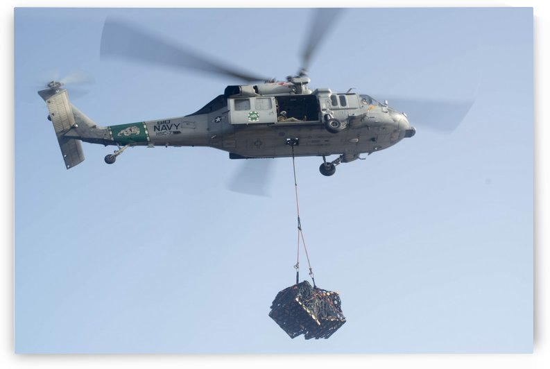 An MH-60S Knighthawk delivers cargo. by StocktrekImages