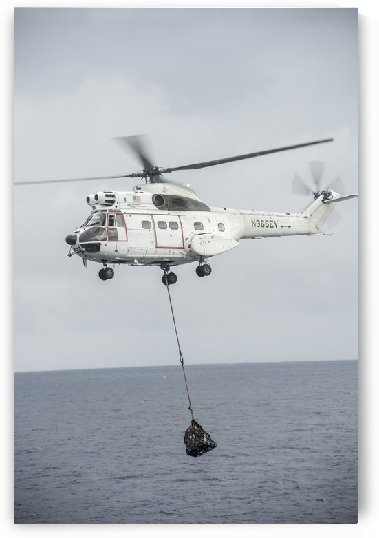 An SA-330 Puma transport helicopter moves cargo during a vertical replenishment. by StocktrekImages