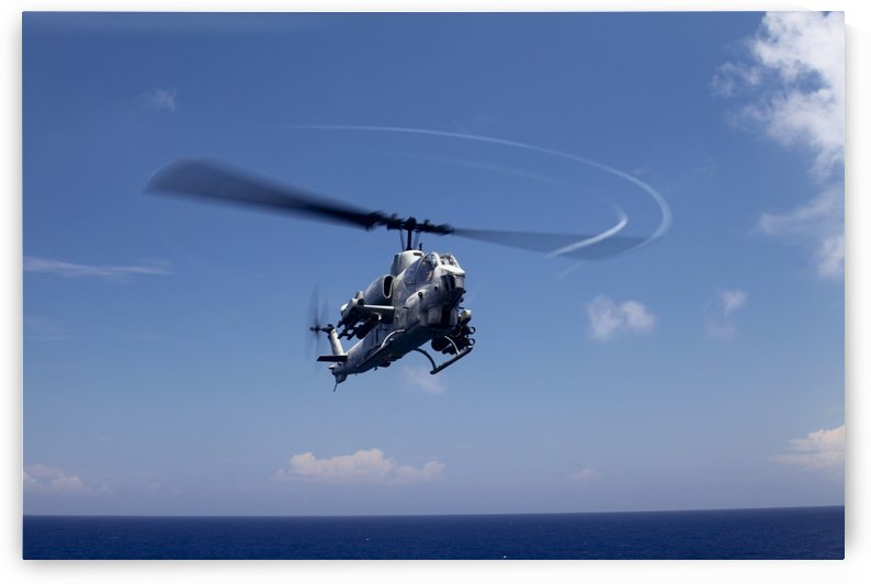 An AH-1 Cobra in flight over the Philippine Sea. by StocktrekImages