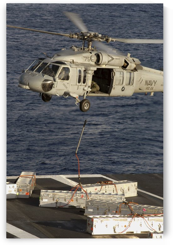 An MH-60S Seahawk delivers ammunition onto the flight deck of USS Theodore Roosevelt. by StocktrekImages