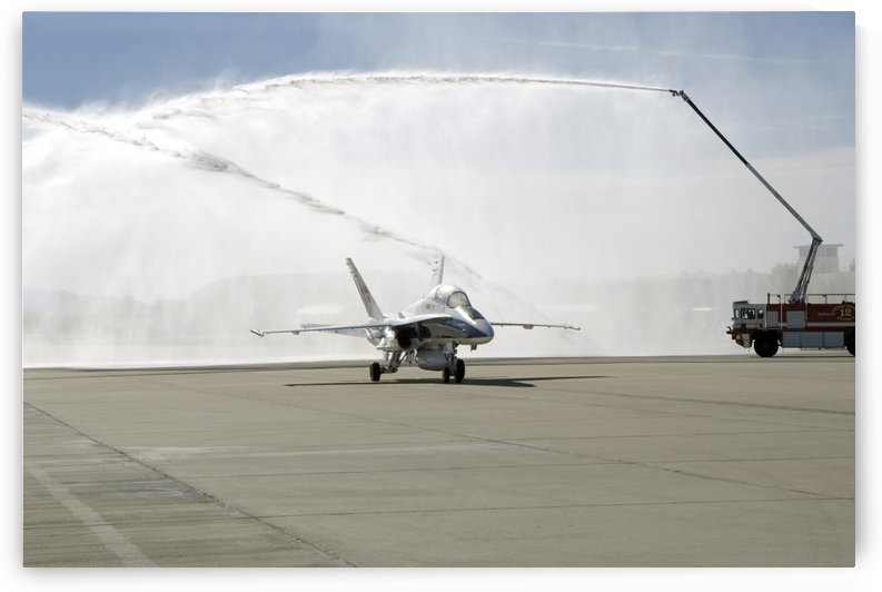 An F-18 aircraft taxies beneath the spray from fire trucks. by StocktrekImages