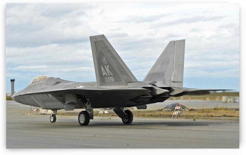 An F-22 Raptor taxis the runway on Elmendorf Air Force Base Alaska. by StocktrekImages