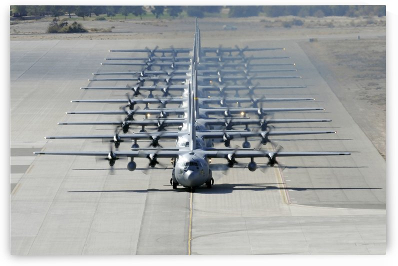 A line of C-130 Hercules taxi at Nellis Air Force Base Nevada. by StocktrekImages