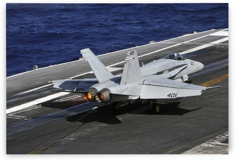 An F-A-18C Hornet lands on the flight deck of USS Abraham Lincoln. by StocktrekImages