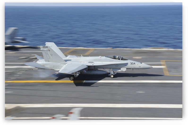 An F-A-18C Hornet lands aboard USS George H.W. Bush. by StocktrekImages