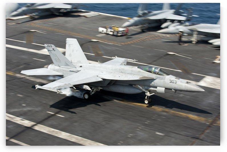An F-A-18E Super Hornet hooks an arresting gear wire while landing. by StocktrekImages