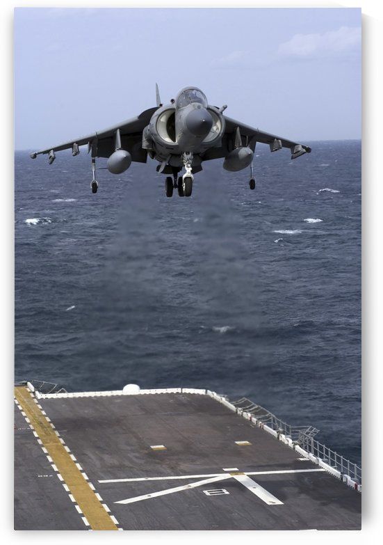 An AV-8B Harrier II prepares to land on the flight deck of USS Nassau. by StocktrekImages